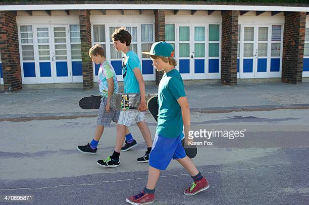 Three boys carrying skateboards
