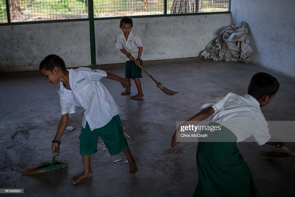 Three boys celanup their class room after school at the Ahlal Taik Monastery School in Dala Township on February 11, 2013 in Yangon, Burma. The school provides basic education for orphans and children from poor areas. As the country goes through sweeping political and economic reforms, many are hopeful that after decades of neglect the healthcare system will also benefit from the changes. Although health budgets have increased the state health system is still underfunded and struggles to provide basic healthcare as well as essential medicines for treating HIV, Malaria and TB. With sanctions being lifted it is hopeful that again the flow of medical equipment, medicines and the presence of NGO's will increase.