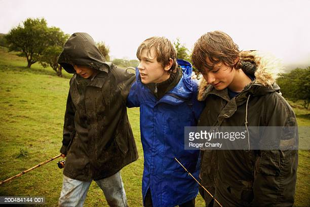 Three boys (14-16) crossing field, two holding fishing rods