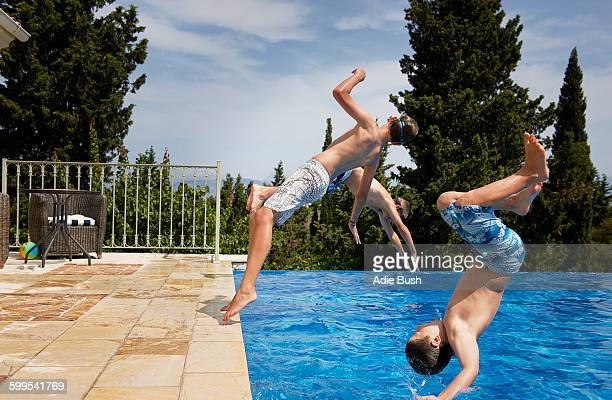 Three boys diving backward into apartment swimming pool