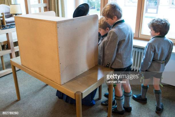 Three boys dressed in traditional Bavarian clothes wait for her mother as she fills in her election ballots at a polling station during German...