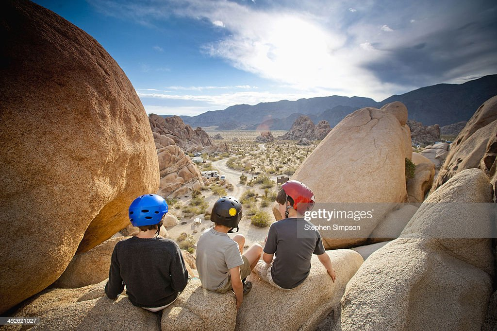 three boys explore boulders at sunrise