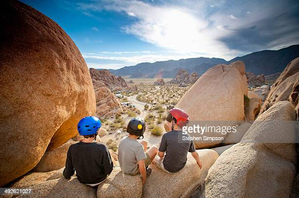 three boys explore boulders at sunrise