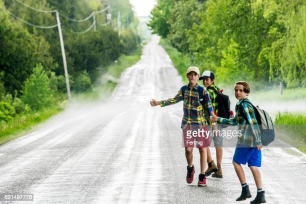 Drei jungen Trampen auf einer Landstraße