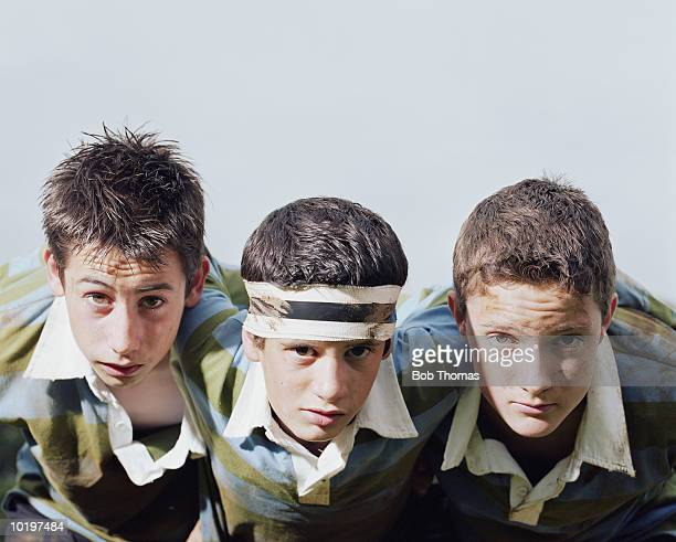 Three boys (12-14) in scrum, portrait, close-up