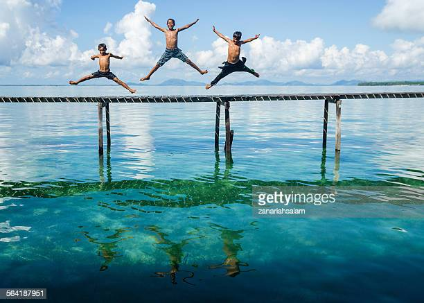 Three boys jumping in to the sea from a jetty, Salakan Island, Semporna, Sabah, Malaysia