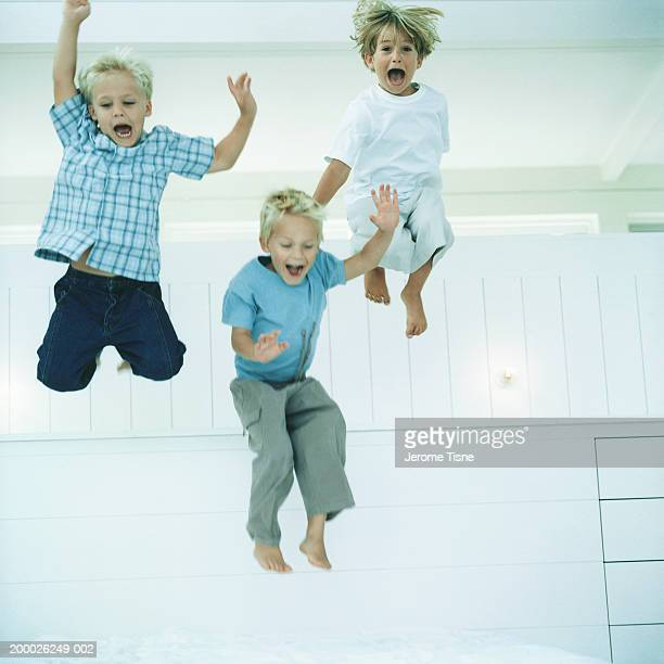 Three boys (4-6) jumping, indoors