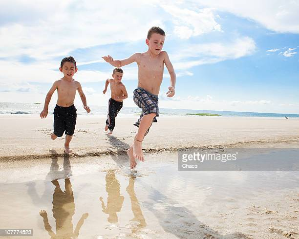 Three boys jumping over a puddle