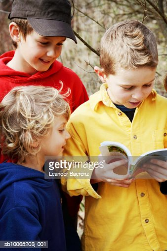 Three boys (7-9 years) looking at guide book, outdoors