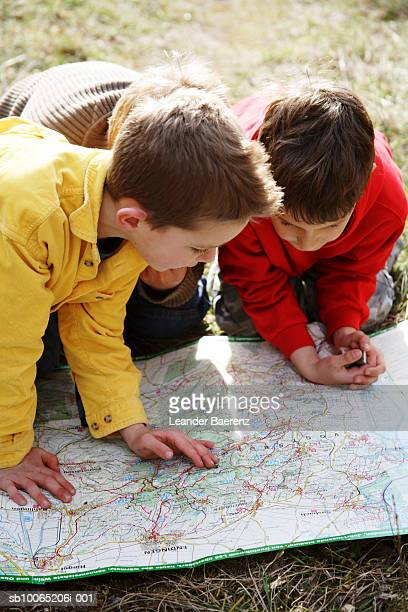Three boys (7-9 years) looking at map on ground, elevated view