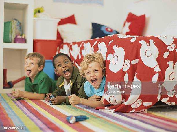 Three boys (6-8) lying under bed pulling faces