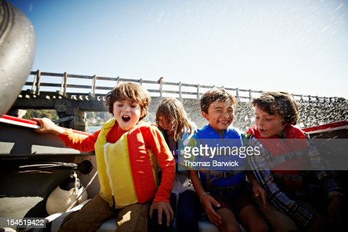 Three boys one girl sitting in boat being splashed : Stock Photo
