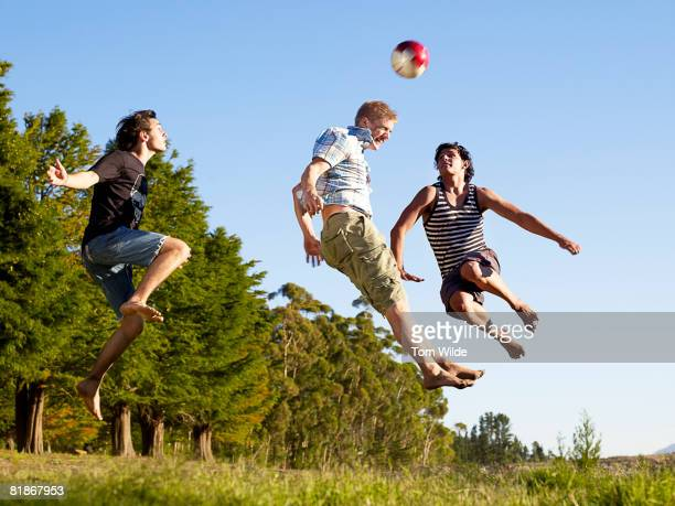 Three boys playing football