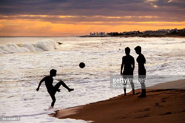 Three boys playing soccer at the beach