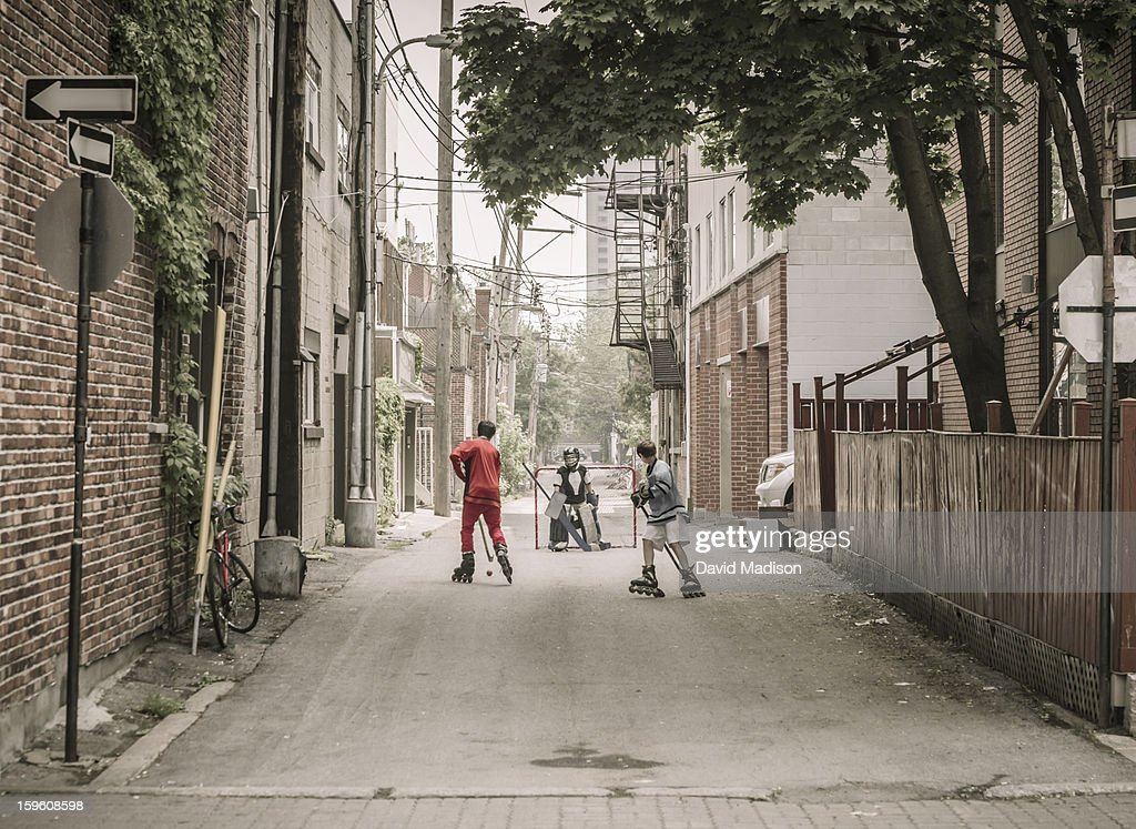Three boys playing street hockey : Stock Photo