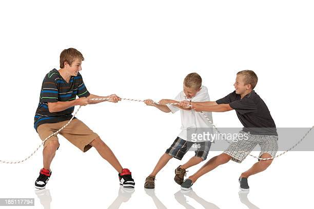 Three boys playing tug-of-war