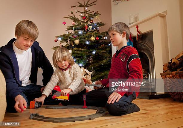 Three boys playing with a train set
