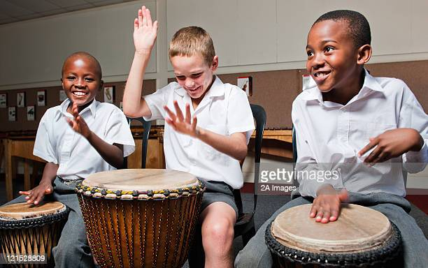 Three boys playing wooden hand drums in classroom, Johannesburg, Gauteng Province, South Africa