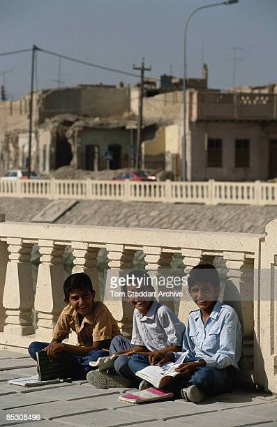 Three boys reading on the pavement in Basra Iraq September 1989
