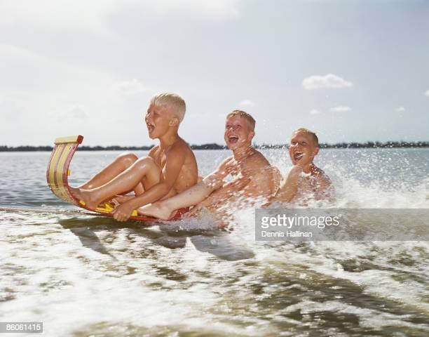 Three Boys Riding Water Sled