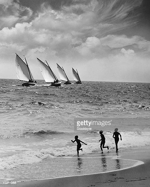 Three boys running along beach, following four sailboats out on ocean