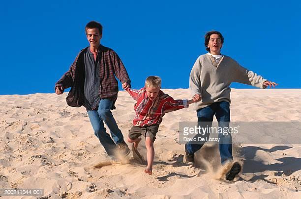 Three boys running on sand