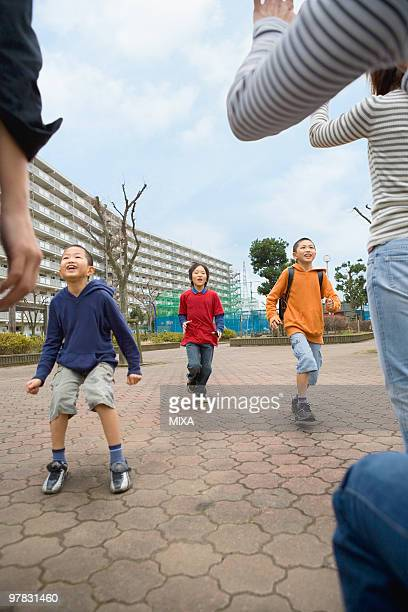 Three boys running to mothers