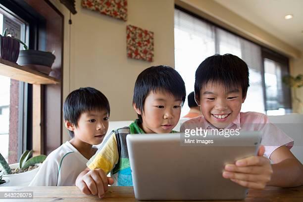 Three boys sitting at a table, looking at a digital tablet, smiling.