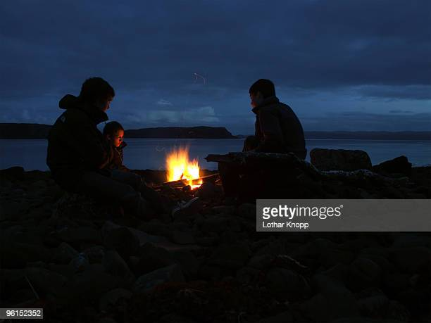 Three boys sitting at campfire