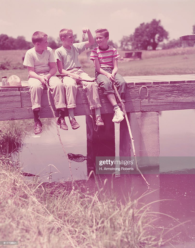 Three boys sitting on pier, using twigs as fishing rods. (Photo by H. Armstrong Roberts/Retrofile/Getty Images) : Stock Photo