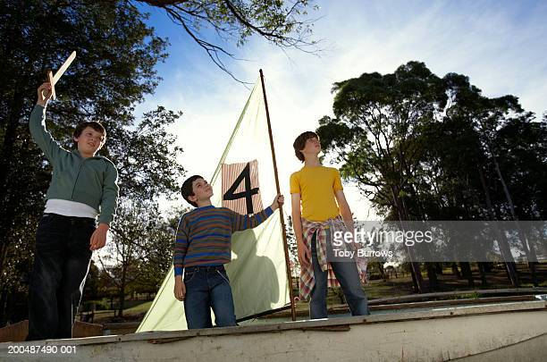 Three boys (9-13) standing in boat, one holding sword, low angle view