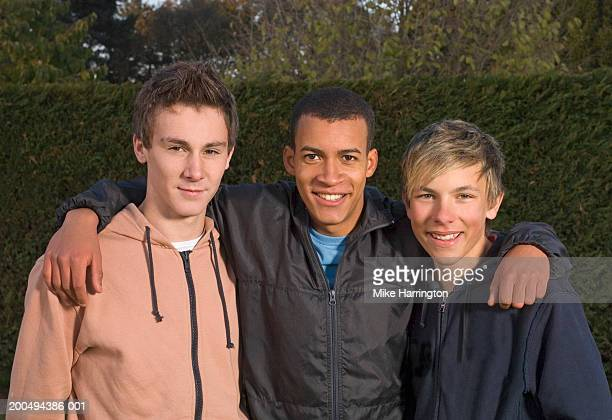 Three boys (15-17) standing together outdoors, smiling, portrait
