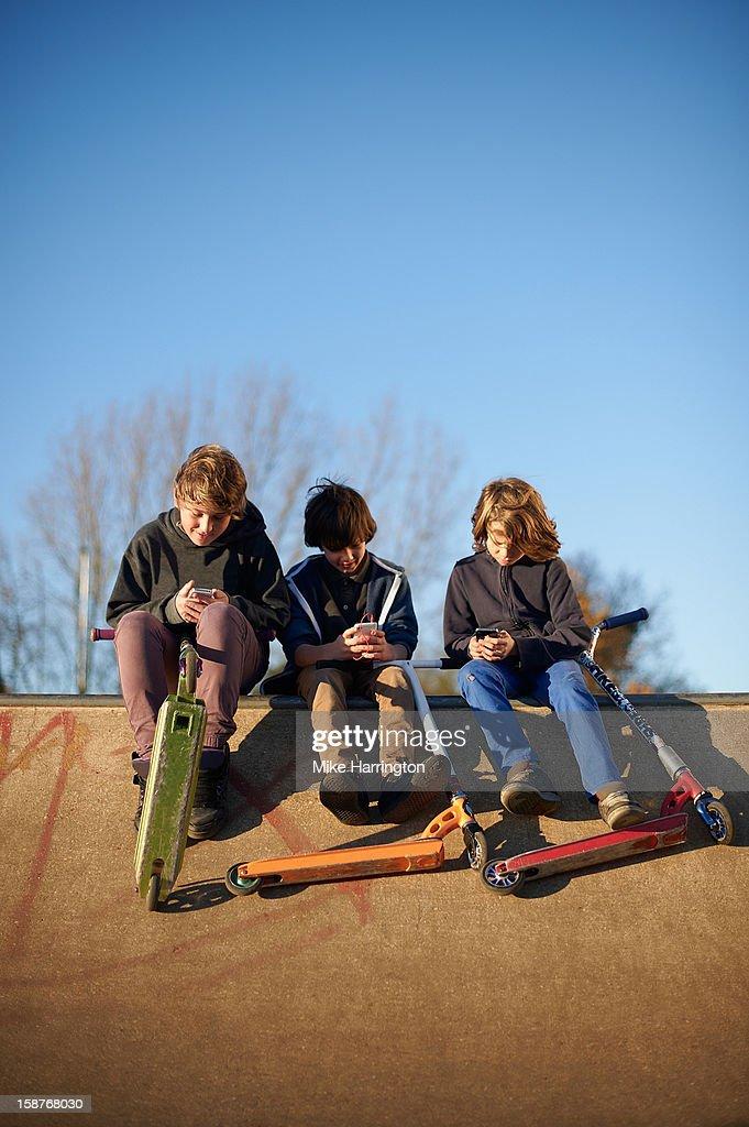 Three boys using mobile phones at skate park : Stock Photo