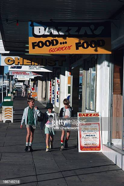Three boys walk down the pavement or sidewalk on a small street in the small outback mining town of Mount Isa under shop signs advertising a chemist...