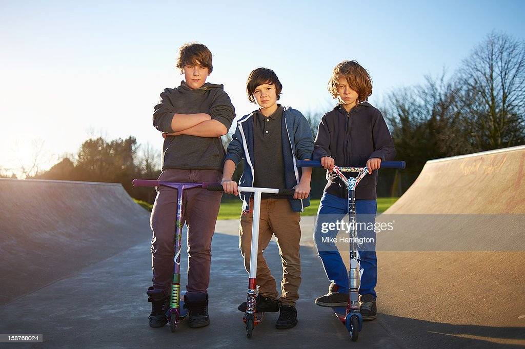 Three boys with micro scooters, looking to camera : Stock Photo