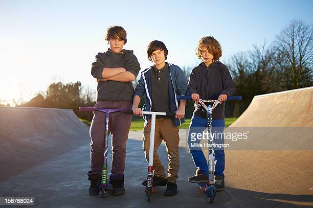 Three boys with micro scooters, looking to camera