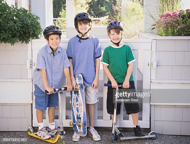 Three boys (7-12) with skateboard and push scooters, portrait