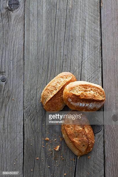Three bread rolls on grey wood