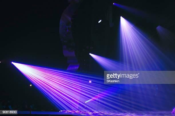 Three bright purple spot lights beaming down