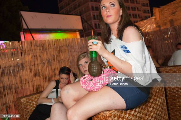 Three British girls drinking grenade themed cocktails at a bar stop on the Party Crewís Letís Go F**king Mental bar crawl Tourists can expect a...