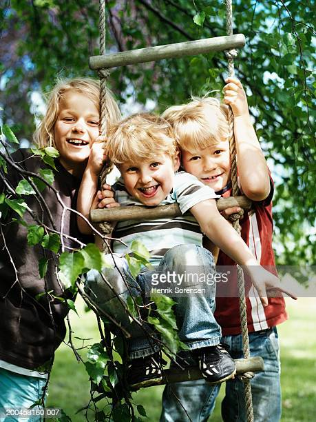 Three brothers (4-9) on rope ladder in garden, smiling, portrait
