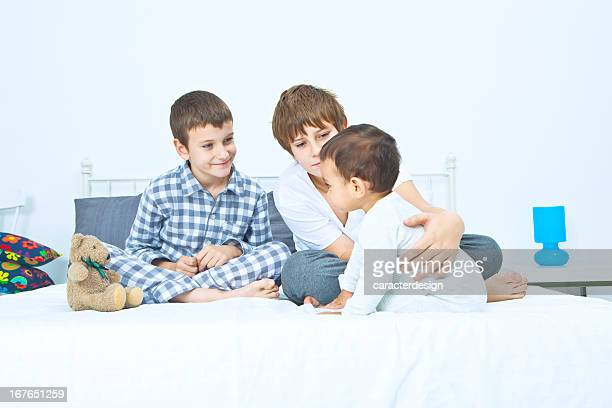 Three brothers sitting on bed