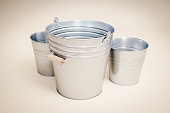 three metal buckets on a smooth beige background