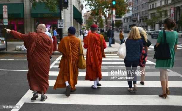 Three Buddhist monks cross a street as three women on a lunch break walk next to them in Washington DC on October 23 2017 / AFP PHOTO / ANDREW...