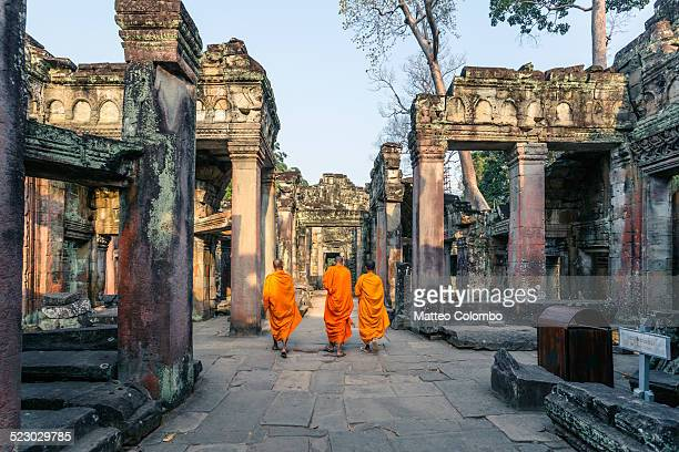 Three buddhist monks walking inside Angkor wat