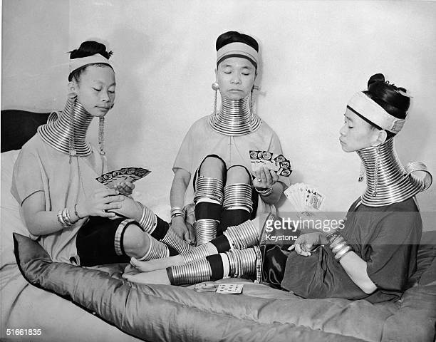 Three Burmese women members of a circus play cards as they wear the brass neck and leg rings traditionally worn by Padaung women since childhood and...