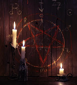 Three burning candles against the background of wooden planks with bloody pentagram. Halloween concept, black magic ritual or satanic spell with occult and esoteric symbols