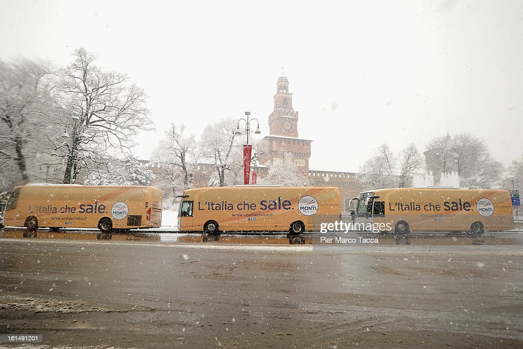 Three buses of the electoral campaign of Mario Monti parked under the snow in Castle plaza on February 11, 2013 in Milan, Italy.Wind, snow and tempetarture under zero over the country has affected regions from North Italy to South Italy, transports has been affected with train cancellations and road closures.