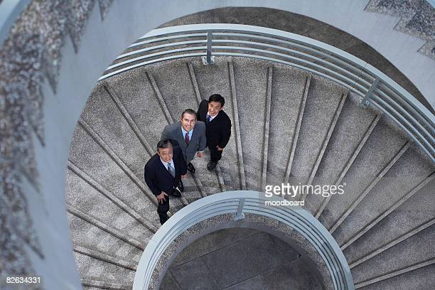 Three business associates standing on spiral staircase, portrait