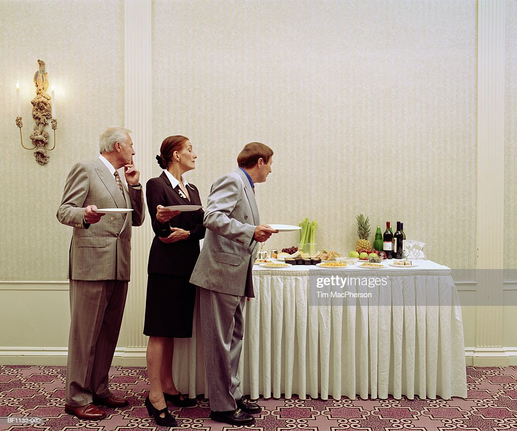 Three business executives queueing for buffet, profile : Stock Photo